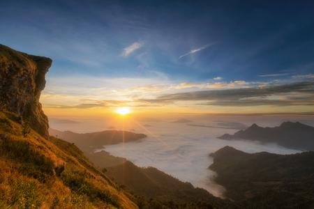 Montaña y acantilado con niebla en sunrise en phucheefah, provincia de Chiang Rai, Tailandia con la pequeña tienda de campaña iluminada adentro. Camping de noche. Paisaje, recreación y colección de fotos al aire libre. Foto de archivo - 72424181
