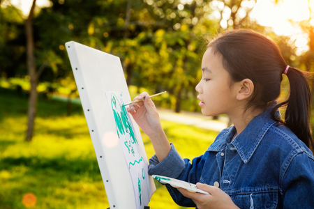 little painter at work in the park with palette and canvas, butter fly drawing with gild in park wint green outdoor backgroung, kid, teen and student concept. Standard-Bild