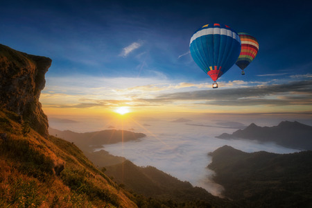 mountain and cliff with fog on sunrise at phucheefah, chiang rai province, thailand with Small Camping Tent Illuminated Inside. Night Hours Campsite.  Landscape, Recreation and Outdoor Photo Collection. Stock Photo