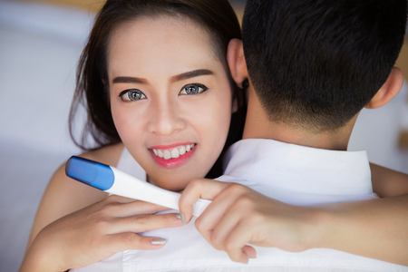 pregnancy test: Closeup of happy young asia woman embracing man after positive pregnancy test, new mother