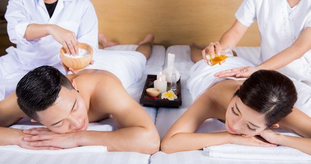 Young couple lying on the massage table and smiling, spa concept