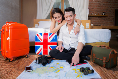 Young couple planning honeymoon vacation trip with map from they room in resort.