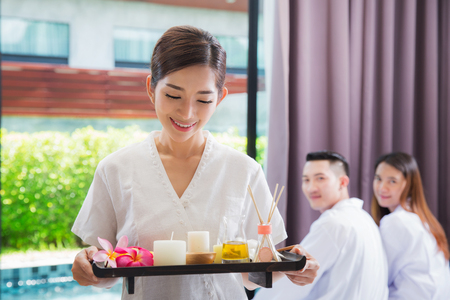 Asian Smiling masseuse holding a tray at the spa with asia customer pending