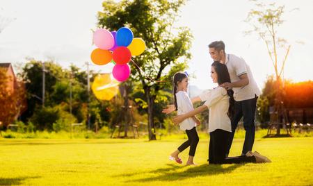 Hija corriendo hacia la madre y el padre, ella disfrutó de los globos de juego.