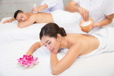 Junges Paar liegt auf dem Massage-Tisch und lächelnd, Spa-Konzept