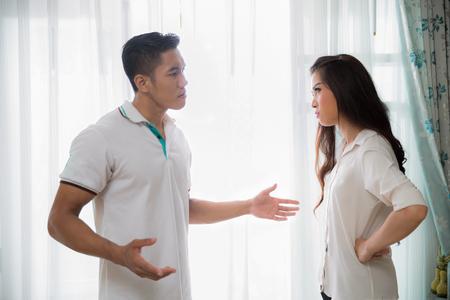 Bild des jungen Mannes Streiten mit seiner Frau zu Hause, während schreit und schimpft seine Frau, Familienkonzept,