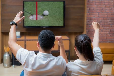 아시아 커플은 거실에서 골프 게임을보고 재미
