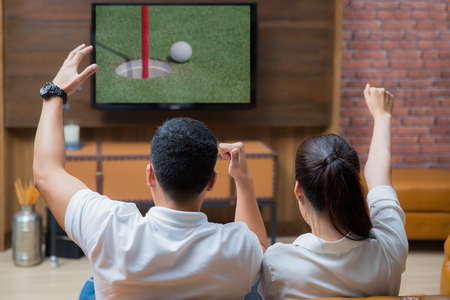 Asian Couple having fun watching golf game in living room Imagens - 72763443