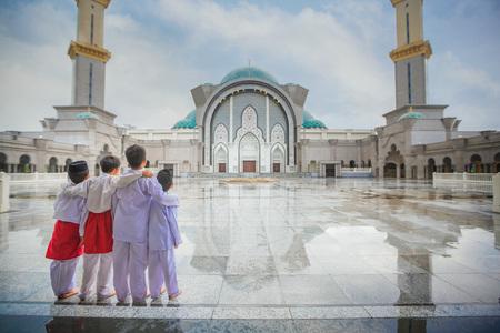 Muslim boy and Masjid Wilayah Persekutuan in Kuala Lumpur, Malaysia