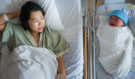 Nieuwgeboren baby, netjes slaap met zijn moeder in het ziekenhuis, mama en babyconcept
