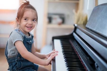 Het meisjesspel piano en zingt een lied in woonkamer, muziek, jong geitje, baby, kindconcept