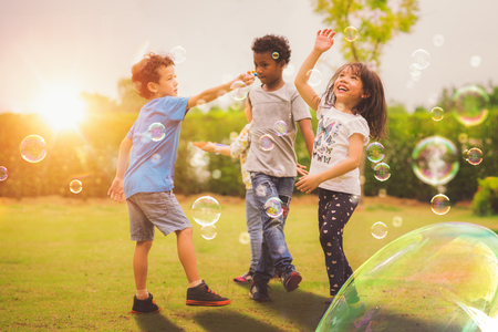 Kid and friends in international pre school play a bubble in playground with sunset background, kid, child, school, play and summer background