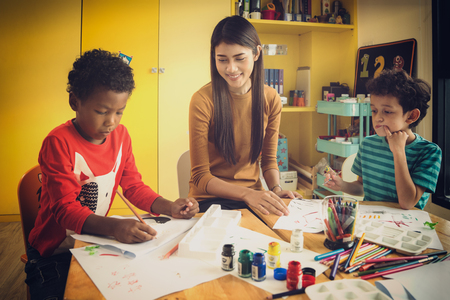 Asian lady teacher in an internation prechool and teach art and drawing subject to american boys, kid, education, child, and study concept