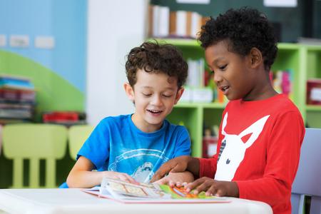 Studente in scuola materna internazionale che legge insieme un libro della rivista nel concetto di biblioteca, di istruzione, del bambino e di studio di scuola