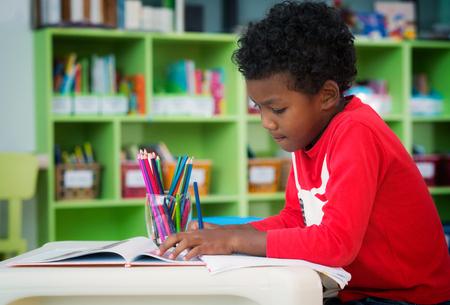 Amerikanischer Junge lässt Haus tragen und in Vorschulbibliothek, Bildung, Kind und Schulkonzept zeichnen