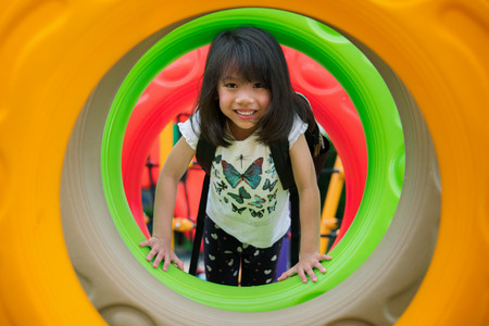 Asian kid fun and happy from play a donus ring in playgroung in her pre school, outdoor, kid,children, education concept