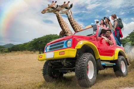 Offener Zoo der asiatischen Freundgruppenreise durch Savanne und Tierkonzept