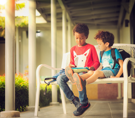 Anerican boy play game in tablet togather in the park, technology, outdoor, computer, internet concept Standard-Bild
