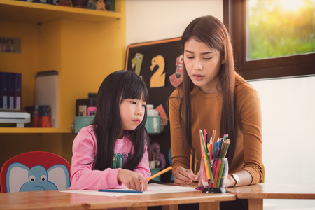 Teacher and student take home work togather in preschool, Library, mother, art, school, teacher, education and kid concept Stock Photo