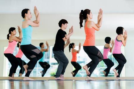 Yoga-Gruppe im Klassenzimmer in Fitness-Center, asiatische Mädchen Team stehen und Aktion im Yoga Standard-Bild