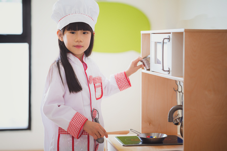 Asian kid in cooking uniform playing a food toy in pre school, kid, educatuin, cooking, and preschool concept Standard-Bild