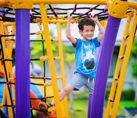 A boy climb a rope in playground in preschool, kid, child, play and fun concept