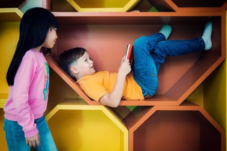 A boy sleep and read a magazine in library in an international preschool, education, kid, and school concept