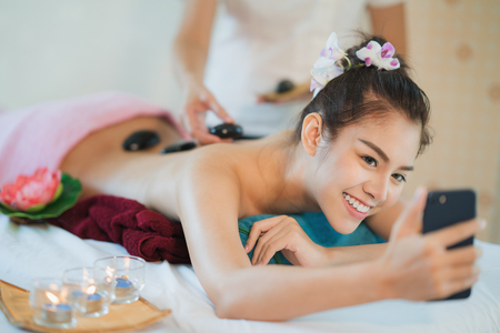 Asian lady take selfie from her mobile phone between massage and stone therapy care and treatment