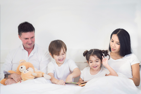 Father, Mother, Brothers and sister read a bedtime story togather on the bed in bedroom, kid, child, family, study, education and home work concept Standard-Bild