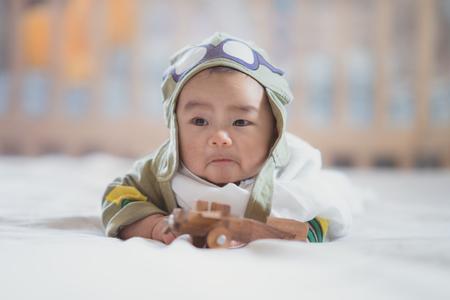 Asiatischer Junge in uniformem Spielluftflugzeug des Japan-Luftwaffensoldats bewaldetes Modell auf dem Schlafzimmer mit ratro Ton, Traum, Kind, Job, Arbeit, Krieg und Babykonzept