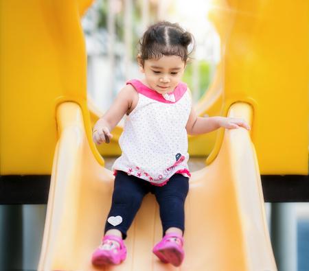 Asiatisches Mädchenspiel ein Schieber im Spielplatz in ihrem Schul-, Kinder- und Spaßkonzept Standard-Bild