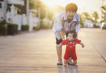 grandmother try to traning a baby for walking in village, bewborn, family