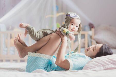 Mutterspiel mit ihrem Baby nach walkup auf dem Bett im Schlafzimmer mit rosa Stimmung, Mutter, Mutter, Kind, Traum, Babyspiel und Kinderkonzept Standard-Bild