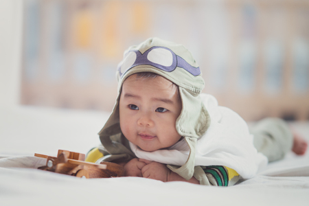 Asian boy in Japan air force soldier uniform play air plane wooded model on the bedroom with ratro tone, dream, kid, job, work, war, and baby concept Standard-Bild
