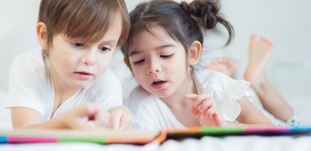 Brüder und Schwester lasen eine Gutenachtgeschichte zusammen auf dem Bett im Schlafzimmer, im Kind, im Kind, in der Familie, im Studium, in der Ausbildung und im Hauptarbeitskonzept