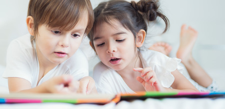 Brothers and sister read a bedtime story togather on the bed in bedroom, kid, child, family, study, education and home work concept Stock Photo