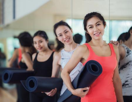 Yogalehrer und ihr Student tragen eine Matte und warten in der Eignungmitte vor Übung, Yoga, Eignung, Training und Gesundheitskonzept