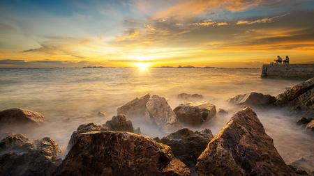 sea sand rock beach and sunset with fishing and fisherman Standard-Bild