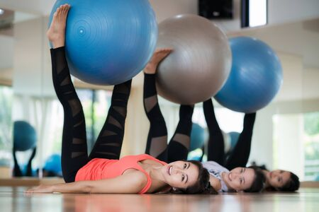 Lady take Ball exercise in fitness center, aerobics with ball group with gym trainner, health, sport, relax and fitness concept Standard-Bild