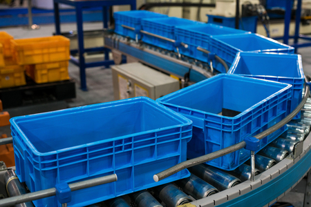 Caixa de plástico na linha de rolos para a produção de transferência de peças na prodine lin na fábrica, produção, conceito de transporte Foto de archivo