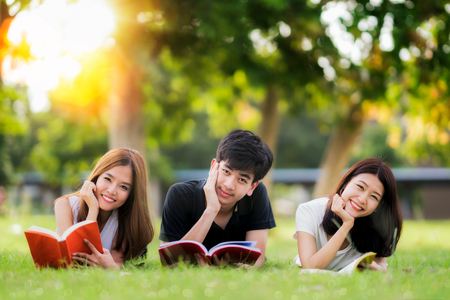 Asian student and friend relax and read a book in university, education and student concept