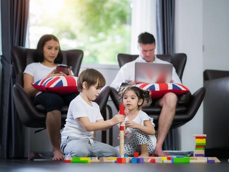 Familie im Wohnzimmer, kleines Kind, Junge und Mädchen spielen bewaldetes Spielzeug