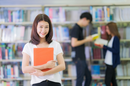 Asian student lady smile and read a book in library in university with her friends, education, student, library and university concept