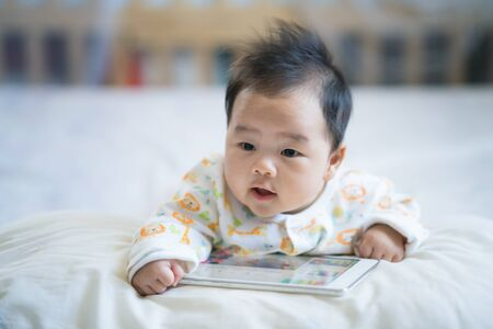 Newborn baby play smart phone on the bed, baby, family and technology concept Stock Photo