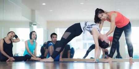 Yogatrainer unterrichten Yogaschüler über diffical Aktion im Yogaklassenzimmer, Eignungsmitteaktivität, Damentrainer unterrichten ihren Studenten. Standard-Bild