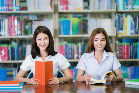 Asian lady student study and do home work in library in University, education and university concept Stok Fotoğraf