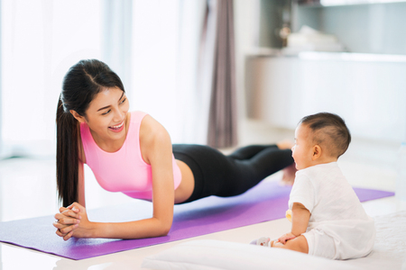 Asian mother fit and play Yoga for lose weight after delivery a new born baby in home, mom, mother, exercise and healthy concept Imagens