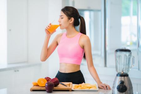 Señora asiática en ropa deportiva de fitness, beba una mezcla de frutas y verduras para obtener belleza, adelgazamiento y salud después de la clase de yoga