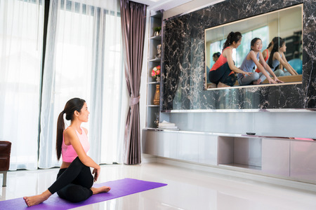 Asian lady start to training Yoga by follow in television in living room, in luxury mome.