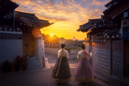 Asian lady in Hanbok dress walk togather in Korea old city with morning sunrise. Imagens